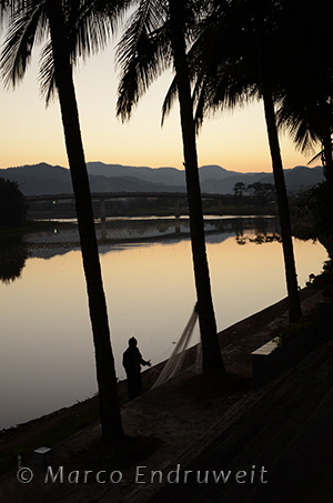A fisherman repairs his nets at the bank of the Luosuojiang River